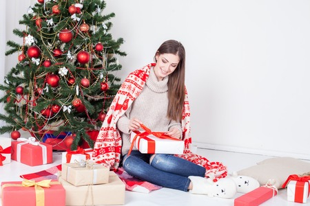 christmastide: the girl looks Christmas gifts at the Christmas tree Stock Photo
