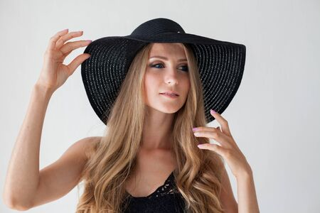 blonde girl with blue eyes a hat with a brim on a white background Stock Photo