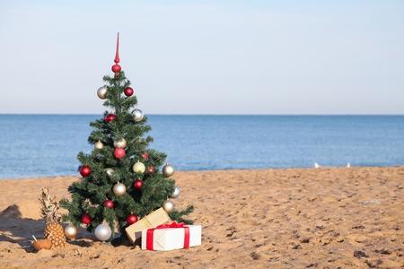 Árbol de navidad con el regalo de resort tropical en la playa.