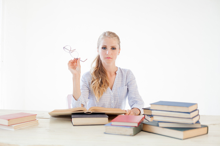female teacher sitting at a table of many books Office Banco de Imagens