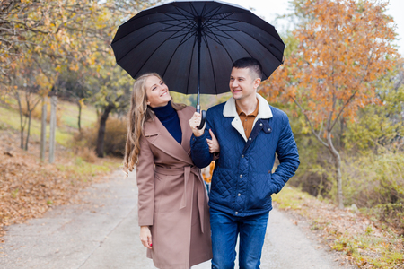 a guy with a girl go under umbrella rain