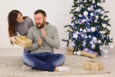 a guy with a girl open Gifts Christmas new year Foto de archivo