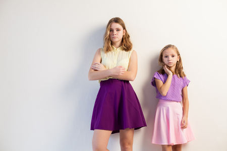 two girls sisters in colored dresses posing