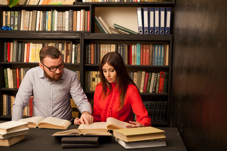 a man and a woman read a lot of books in the library 1