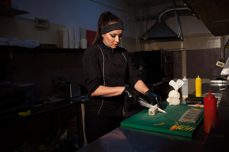 girl sushi chef prepares food in the kitchen at restaurant