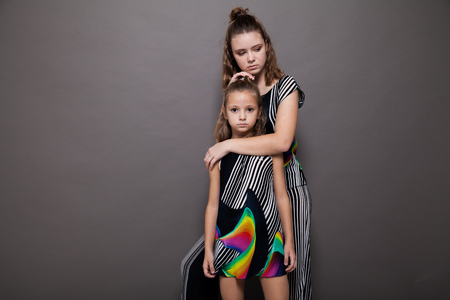 two girls fashionable posing on a grey background
