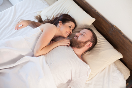 a man and a woman sleeping in beds at home