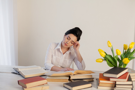 girl asleep at a table with books Stock Photo