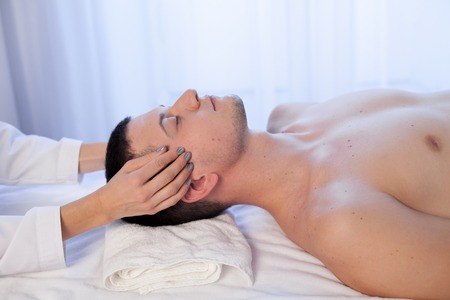 masseuse makes a therapeutic massage of the head and neck man Spa