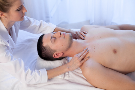 masseuse makes a therapeutic massage of the head and neck man Spa 1