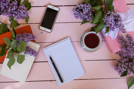 on the white table lilac, gift, notebook, cup of tea