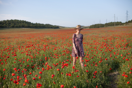 a woman farmer in a field of red poppies