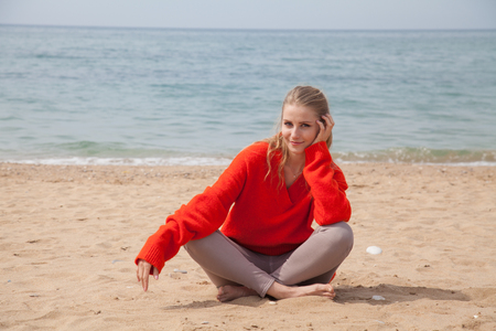 blonde woman sitting alone on a sandy beach Stok Fotoğraf