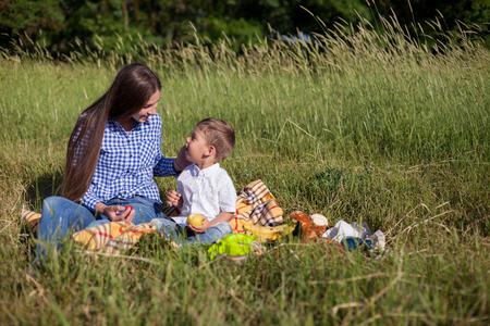 mother and young son eat at a picnic in the forest