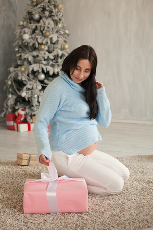 pregnant woman opens new years gift from the Christmas tree