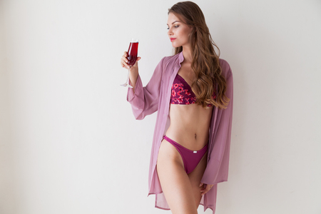 beautiful woman in underwear with a glass of red wine Фото со стока