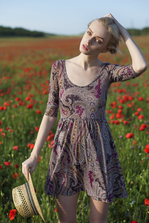 fashionable woman farmer on a field of red poppies