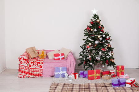 Christmas tree in a white room with Christmas decorations and gifts toys Stock Photo