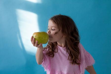 small beautiful girl eating Apple green teeth