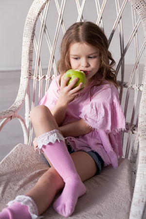 small beautiful girl eating Apple green teeth