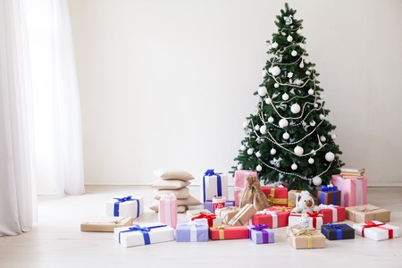 Christmas tree with Christmas gifts in white room Stock Photo