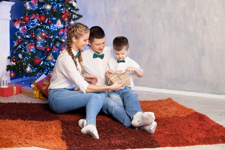 mom dad and a little boy open Christmas gifts for the new year Stock Photo