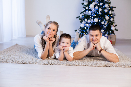 mom dad and a little boy decorate the Christmas tree in winter