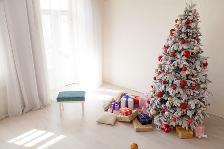Christmas Christmas tree with presents in a white room in winter