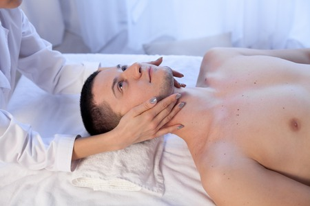 man doing medical massage of the face and neck in Spa