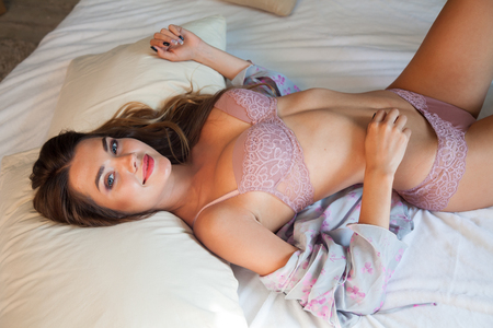 beautiful woman in lingerie is lying on his back with flower