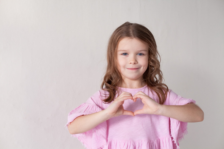 a little girl in a pink dress shows hands heart