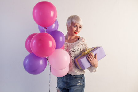 beautiful blonde with balloons and gifts on the holiday