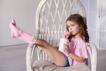 beautiful fashionable little girl sits on the couch and drinking milkshake Archivio Fotografico