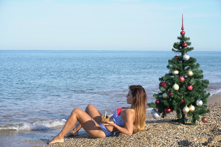 a beautiful woman in a swimsuit sea Christmas new year tree vacation