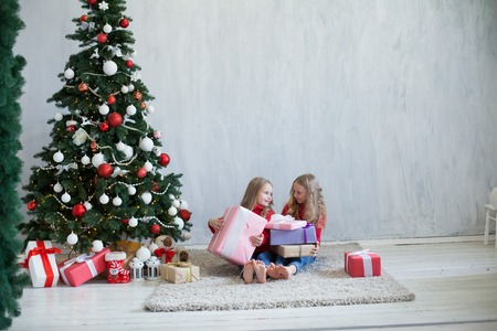 two small girls blonde in red dress at Christmas gifts new year holiday