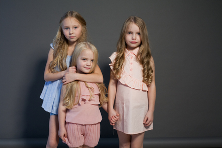 three beautiful little girls sisters portrait fashion grey background