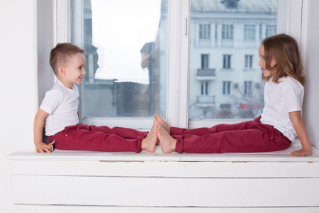 little boy and girl sit on the windowsill looking out the window Standard-Bild