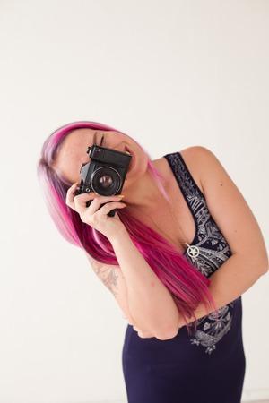 beautiful woman with pink hair makes a snapshot camera