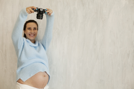 beautiful pregnant woman takes a picture on the camera Stok Fotoğraf