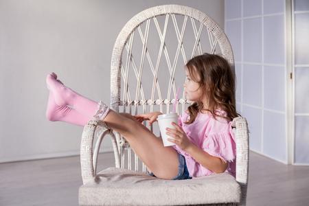 hermosa chica en un vestido rosa sentada en un taburete blanco