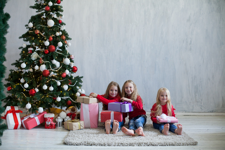 three girls blonde sisters girlfriends gift new year tree holiday Christmas Stock Photo