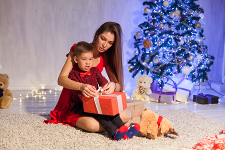 mother and son open up gifts from Christmas New Year holiday house