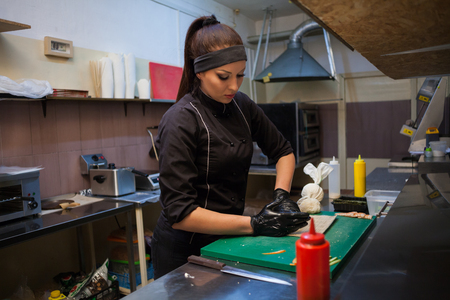 woman prepares delicious sushi in the kitchen at restaurant