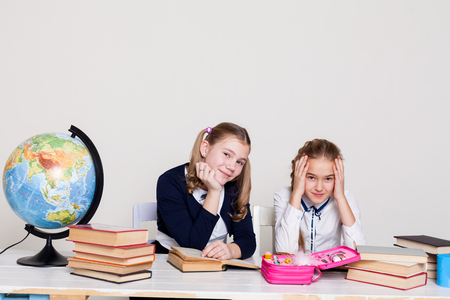 two girls in the classroom Learn lesson books at her desk globe