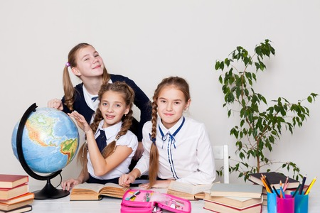 three girls in the classroom studying geography globe of planet Earth