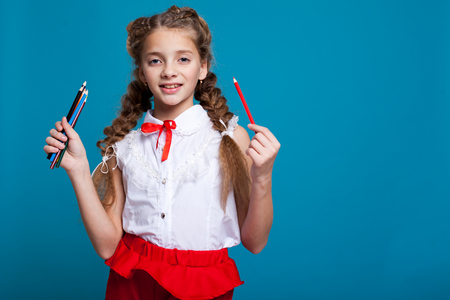 Portrait of beautiful girls with braids with a red pencil on blue background Banque d'images - 113990738