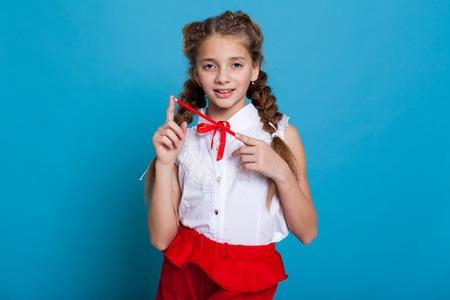 Portrait de belles filles avec des tresses avec un crayon rouge sur fond bleu