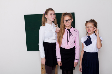three girls in glasses at the Blackboard in a class lesson