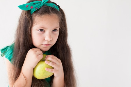 small beautiful girl eating fresh fruit Green Apple