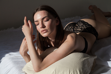 beautiful woman in underwear lies on the bed in the bedroom the morning sleep